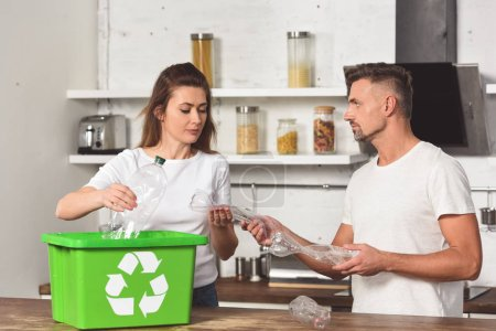 husband and wife standing at kitchen and putting empty plastic bottles in recycle box