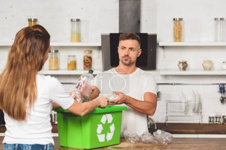adult husband taking plastic bottles and looking at wife with recycle box at kitchen table