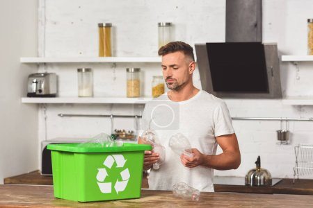adult man holding plastic bottles with green recycle box at kitchen