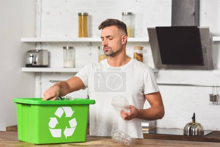handsome man putting plastic bottles in green recycle box