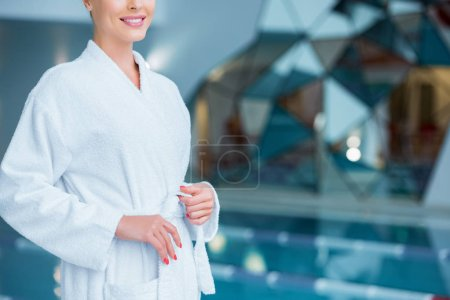 Cropped view of woman untying white bathrobe near pool