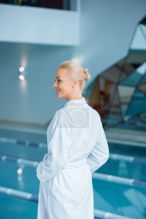 Beautiful woman standing in bathrobe near pool