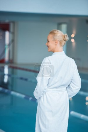 Woman standing in white bathrobe in spa