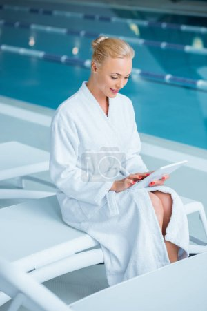 Beautiful woman sitting on deck chair with digital tablet