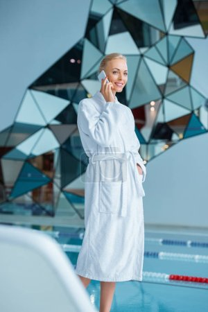 Beautiful woman standing in bathrobe and taking on smartphone