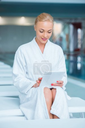 Beautiful woman sitting in bathrobe with digital tablet