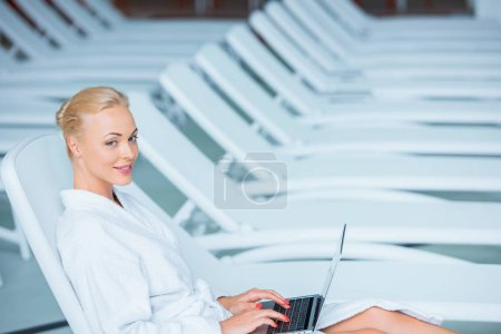 Beautiful woman using laptop in bathrobe