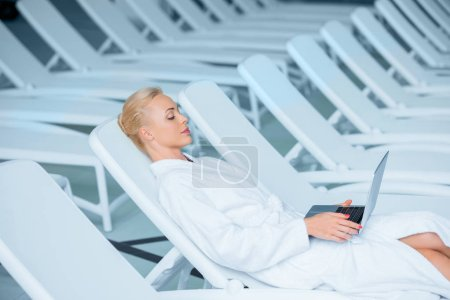Beautiful woman lying on deck chair with laptop