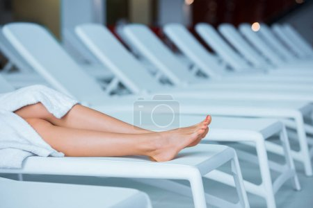 Cropped view of woman legs lying on white deck chair