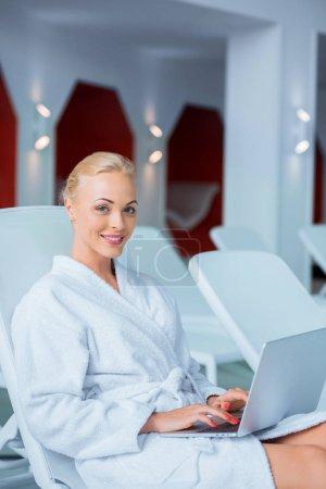 Beautiful woman typing on laptop in white bathrobe
