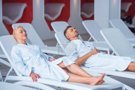 Photo pour Couple reposant sur des chaises en peignoir blanc - image libre de droit
