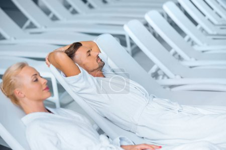 Couple relaxing on deck chairs in white bathrobes