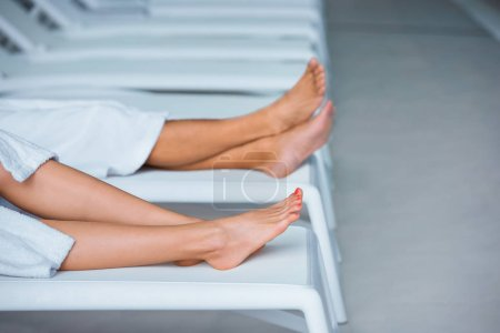 Cropped view of man and woman legs on deck chairs