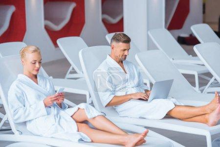 Photo pour Mari et femme se trouvant sur les chaises longues et à l'aide d'appareils numériques - image libre de droit
