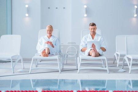 Photo pour Heureux mari et la femme se trouvant sur les chaises longues avec des appareils numériques - image libre de droit