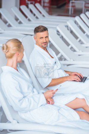 Cheerful husband lying on deck chair with laptop and looking at wife