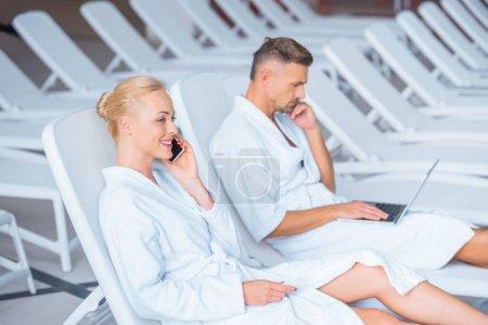 Photo pour Femme parlant sur smartphone alors que mari à l'aide d'ordinateur portable - image libre de droit