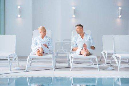 Photo pour Couple gai se trouvant sur les chaises longues avec des appareils numériques - image libre de droit