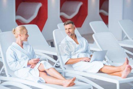 Photo pour Couple heureux couché sur les chaises longues avec des appareils numériques - image libre de droit