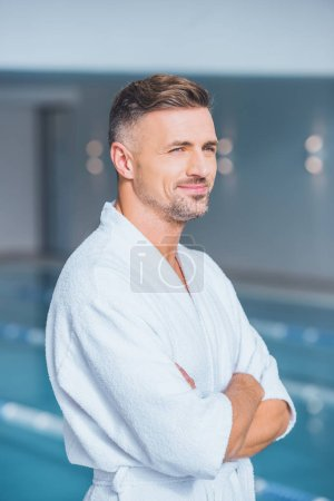 Handsome man standing in spa with crossed arms