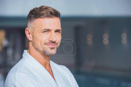 Close up of handsome man smiling in white bathrobe