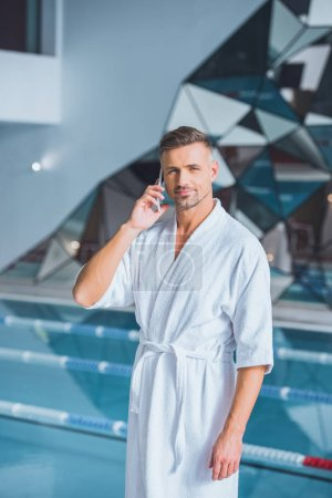 Handsome man talking on smartphone in spa