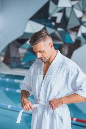 Handsome man untying bathrobe near pool