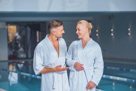 Photo pour Commandes de couple heureux en peignoirs en spa - image libre de droit
