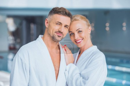 Cheerful couple standing and smiling in bathrobes