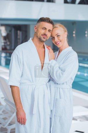 Photo pour Couple heureux souriant en peignoirs en spa - image libre de droit