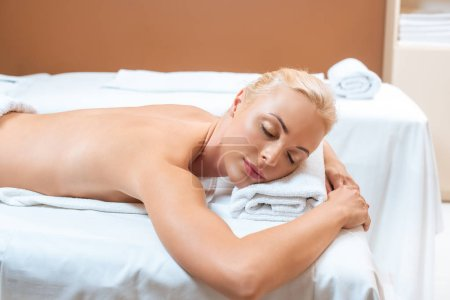 Beautiful woman lying on massage table with closed eyes