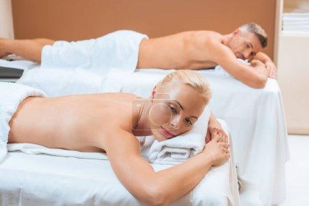 Photo pour Couple de détente sur des tables dans le salon spa de massage - image libre de droit