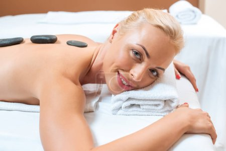 Beautiful woman lying on massage table with hot stones