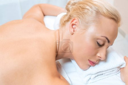 Attractive woman lying on massage table with closed eyes