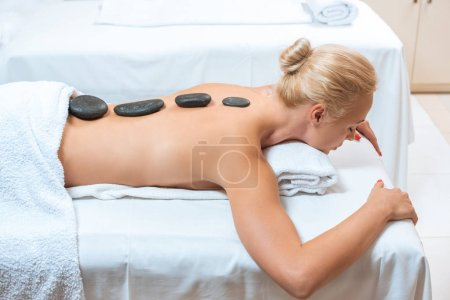 Beautiful woman lying with hot stones on back in spa