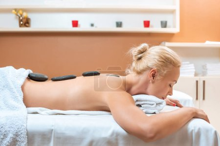 Woman lying on massage table in spa with closed eyes