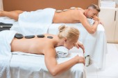 Couple lying with hot stones on back in spa salon
