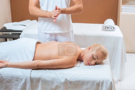 Photo for Male masseur warming hands near woman in spa salon - Royalty Free Image