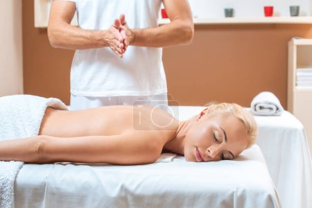 Photo for Male therapist warming hands near blonde woman in beauty salon - Royalty Free Image