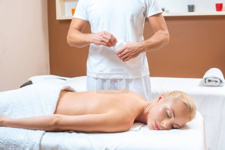 Male masseur opening bottle with oil near blonde woman