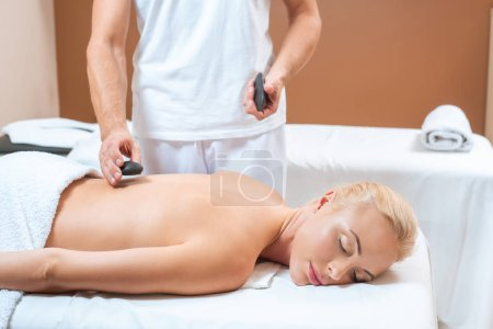 Photo for Male masseur putting hot stones on back of blonde woman - Royalty Free Image