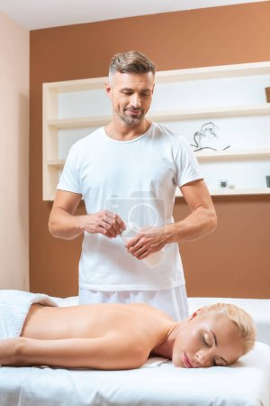 Handsome masseur opening bottle with massage oil and looking on blonde woman