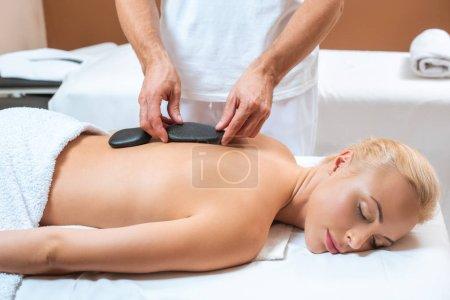Woman enjoying hot stone massage in spa salon