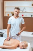 Male masseur smiling and putting hot stones on back of woman