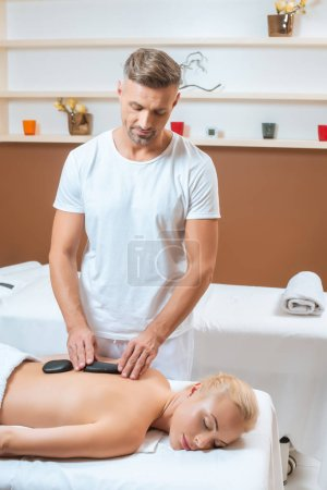 Handsome therapist putting hot stones on back of woman