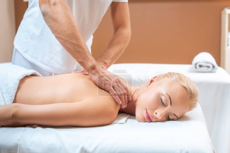 Photo for Blonde woman enjoying massage of male therapist in spa - Royalty Free Image