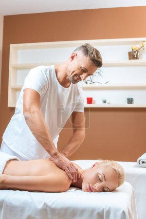 Photo for Handsome masseur doing massage to blonde woman in spa salon - Royalty Free Image