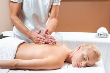 Photo for Male masseur doing back massage to woman in beauty salon - Royalty Free Image