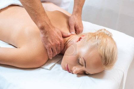 Woman enjoying neck massage in spa salon