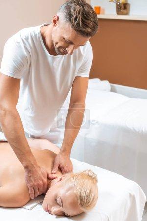 Handsome masseur doing neck massage to blonde woman